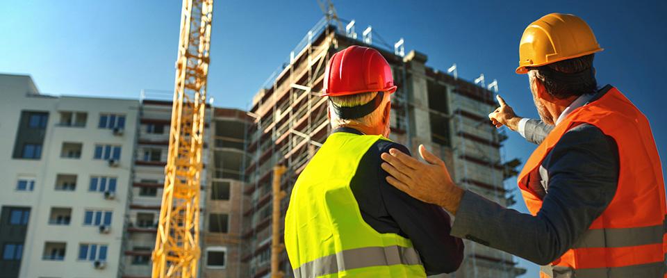 Dwóch mężczyzn rozmawiających patrząc nabudowę bloku