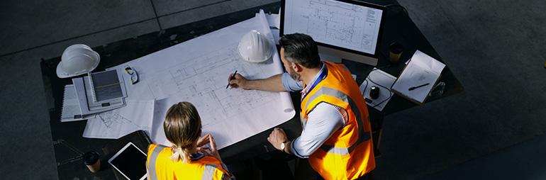 Dwójka pracowników rozmawiająca przy projekcie budowy